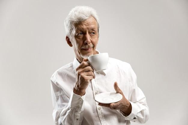 Volkskonzept - glücklicher älterer mann mit tasse tee im studio. konzept der menschlichen emotionen