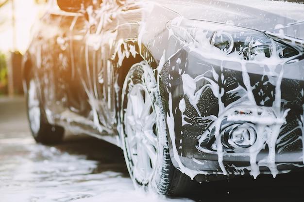 Volksmann, der hand rosa schwamm für das waschen des autos hält. concept car wash sauber.