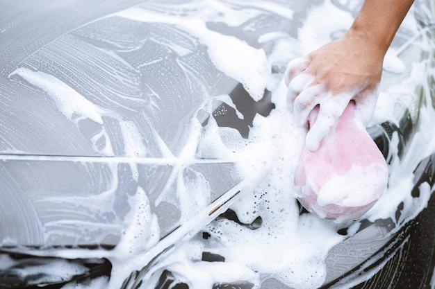 Volksmann, der hand rosa schwamm für das waschen des autos hält. radreifen reinigen. concept car wash sauber.