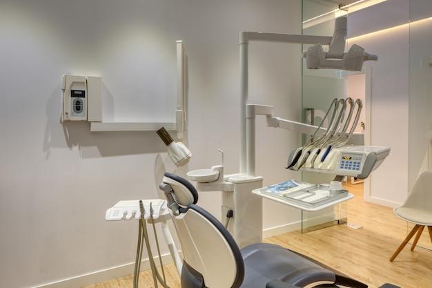 Voll ausgestattete moderne zahnklinikbox mit weißen wänden und holzboden