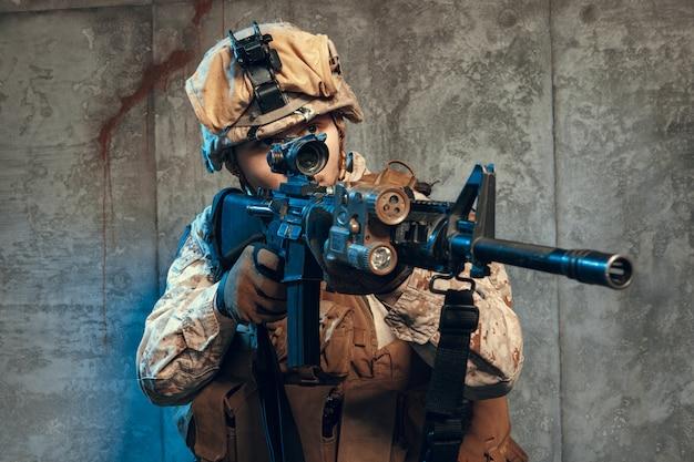 Voll ausgestatteter soldat in tarnuniform und helm, bewaffnet mit pistole und sturmgewehr