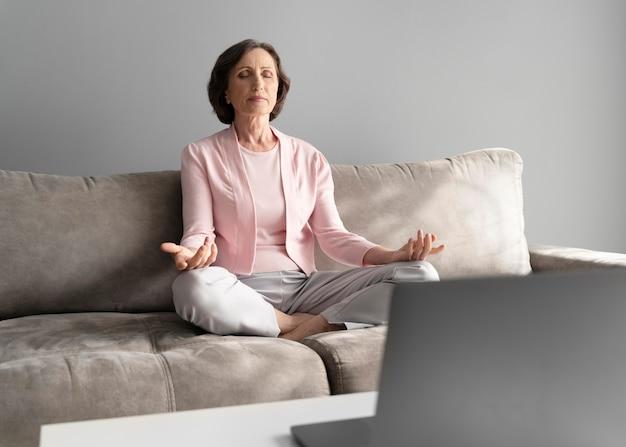 Voll erschossene frau, die auf der couch meditiert