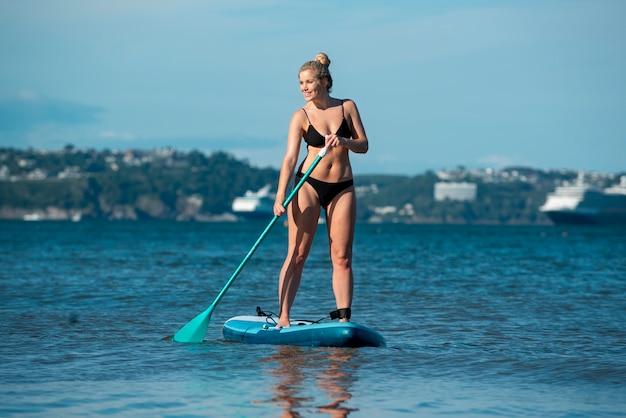 Voll erschossene frau, die auf paddleboard steht