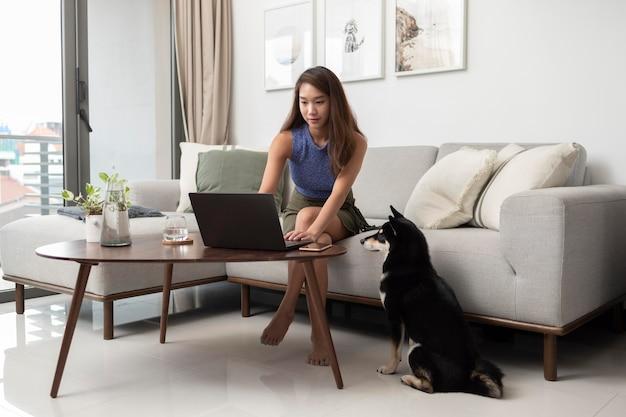 Voll erschossene frau, die mit hund am laptop arbeitet