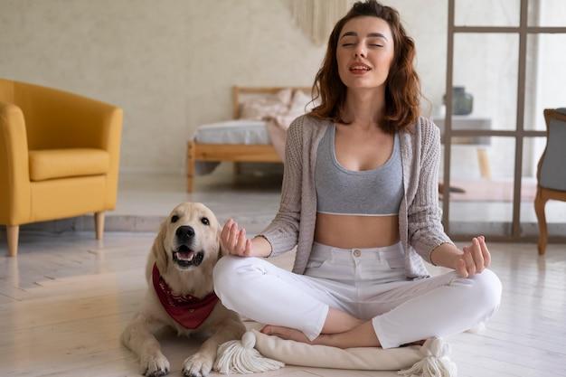 Voll erschossene frau, die mit hund meditiert