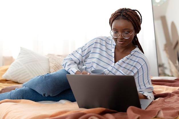 Voll erschossene frau, die sich mit laptop im bett entspannt