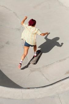 Voll erschossene frau, die spaß auf dem skateboard hat