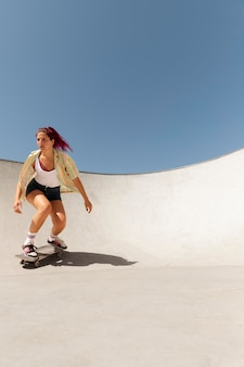 Voll erschossene frau, die tricks auf dem skateboard macht