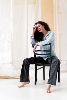Voll erschossene frau sitzt auf stuhl