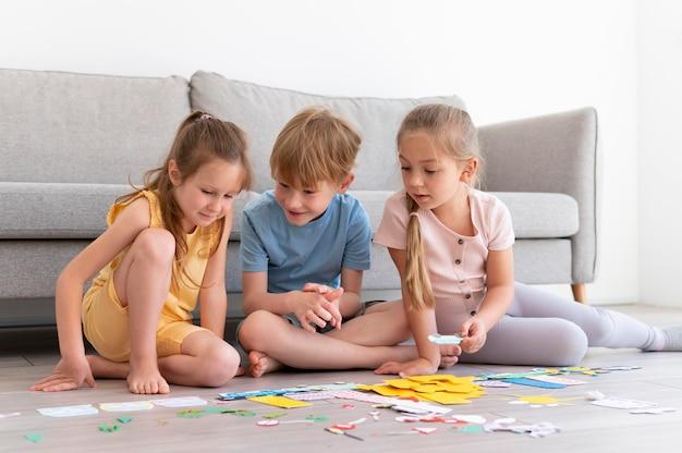 Voll erschossene kinder, die mit papier spielen