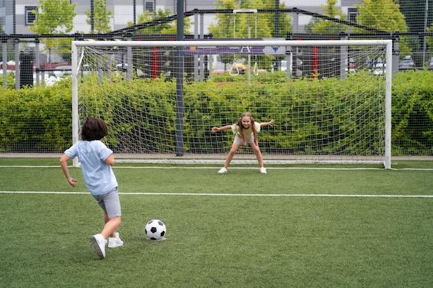 Voll geschossene kinder, die fußball spielen