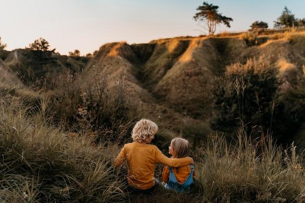 Voll geschossene kinder sitzen auf gras