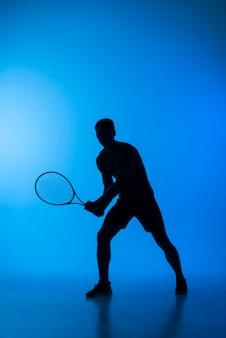 Voll geschossene mannsilhouette beim tennisspielen