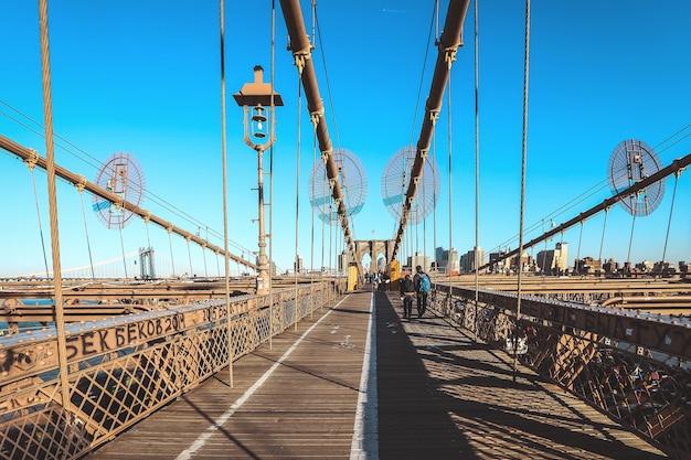 Voll vom touristen, der auf brooklyn-brücke an einem schönen tag, new york geht