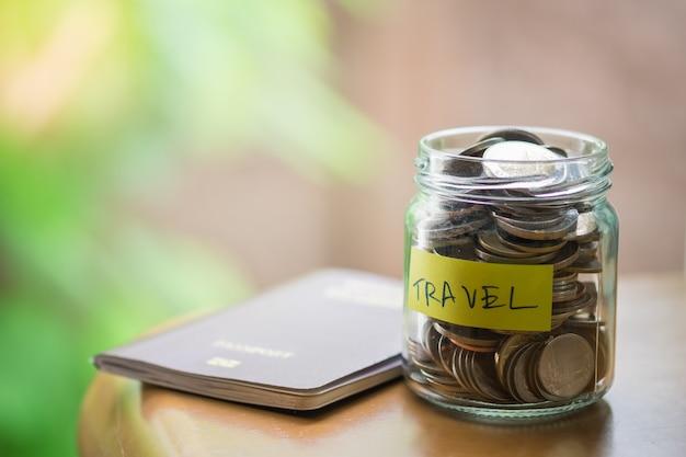 Voll von münzen in der klaren flasche mit gelber aufkleberanmerkung mit reisewort und pass auf holztisch.