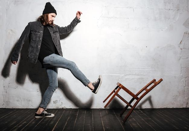 Vollbeiniges porträt eines bärtigen hipster-mannes, der stuhl mit fuß tritt