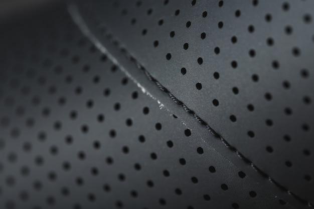 Vollbildnahes schwarzes strukturiertes leder mit perforationen