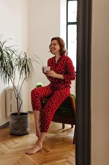 Volle ansicht der lachenden barfüßigen frau, die tasse kaffee hält. glückselige frau im roten pyjama, die am morgen zu hause aufwirft.