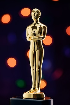 Volle goldene statuette auf defocused lichtern