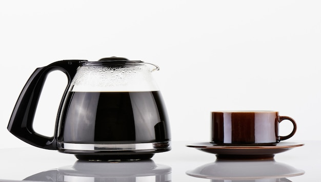 Volle kaffeekanne und braune tasse
