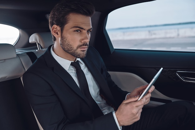 Volle konzentration bei der arbeit. hübscher junger mann im vollen anzug, der mit digitalem tablet arbeitet, während er im auto sitzt