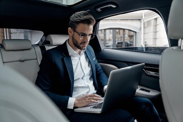 Volle konzentration bei der arbeit. selbstbewusster junger mann im vollen anzug, der mit laptop arbeitet, während er im auto sitzt