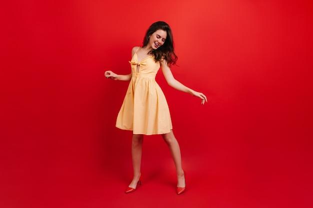 Volle länge aufnahme der aktiven frau, die auf roter wand tanzt. dame im sommerkleid und in den absätzen, die spaß haben.
