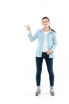 Volle länge aufnahme der jungen lächelnden jungen frau, die am kopienraum zeigt