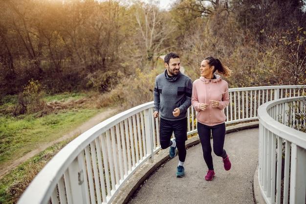 Volle länge begeisterter junger sportlicher heterosexueller freunde, die die brücke besteigen und rennen. fitnesskonzept im freien.