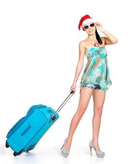 Volle länge der frau in der weihnachtsmütze, die mit reisekoffer steht