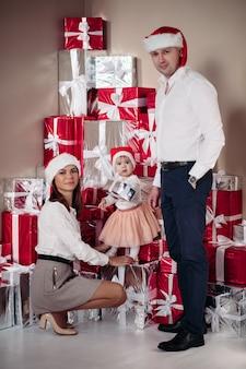 Volle länge der fröhlichen schönen familie mit dem baby, das gegen eingewickelte weihnachtsgeschenke steht