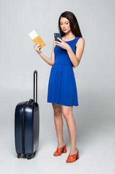 Volle länge der jungen frau im lässigen gehen mit der reisetasche, isoliert