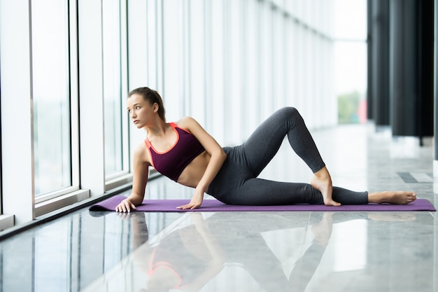 Volle länge der jungen schönen frau in der sportbekleidung, die seitenplanke vor dem fenster im fitnessstudio tut