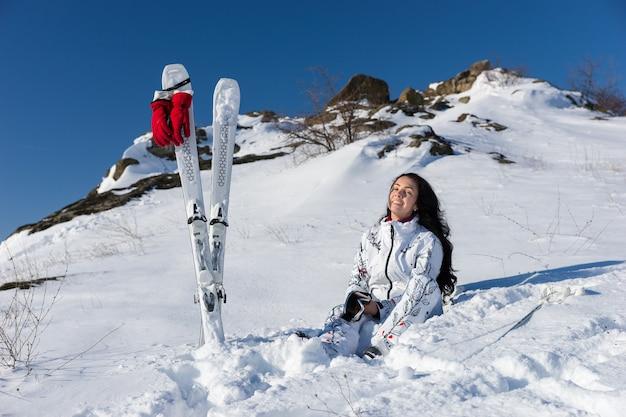 Volle länge der lächelnden jungen frau mit langen dunklen haaren, die auf schneebedecktem berghang mit skiern und stöcken in der nähe sitzt und warmen sonnenschein genießt