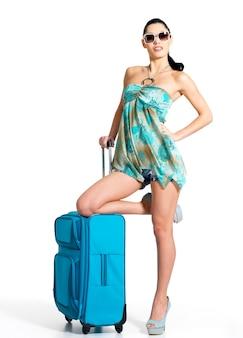 Volle länge der lässigen frau, die mit reisekoffer steht