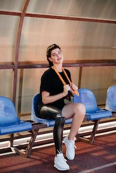 Volle länge der selbstbewussten behinderten sportlerin mit beinprothese, die übungen mit einem springseil am strand macht