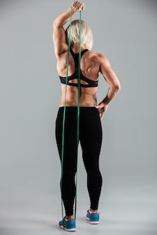 Volle länge der sportlerin in sportkleidung stretching hand mit elastischem gummi