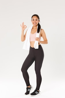 Volle länge der zufriedenen lächelnden sportlerin, niedliches asiatisches mädchen zeigen okay geste nach gutem fitnesstraining, trainingsübungen im fitnessstudio, weißer hintergrund.