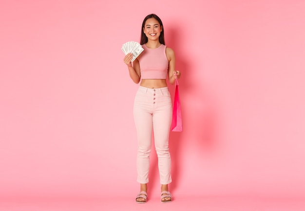 Volle länge des attraktiven lächelnden asiatischen mädchens in der sommerkleidung, das geld und die einkaufstasche hält, etwas teures kauft, genießt, in einkaufszentren zu gehen, rosa wand stehend