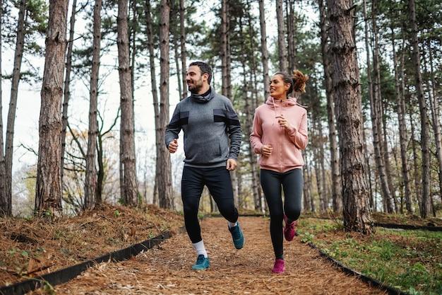 Volle länge des fit-paares, das im herbst durch wälder läuft und sich auf den marathon vorbereitet