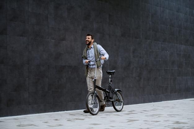 Volle länge des fröhlichen gutaussehenden kaukasischen modischen mannes, der musik hört und fahrrad schiebt. im hintergrund ist graue wand.
