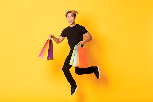 Volle länge des glücklichen attraktiven asiatischen mannes, der vom glück springt und einkaufstaschen trägt, stehende gelbe wand.