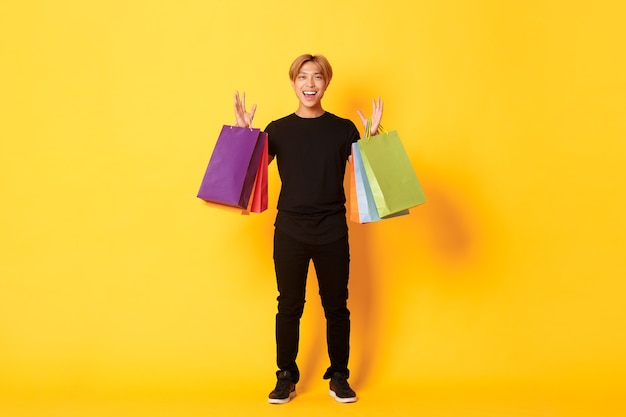 Volle länge des glücklichen gutaussehenden asiatischen kerls beim einkaufen, beim halten von taschen und beim lächeln, gelbe wand.