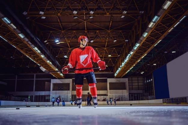 Volle länge des hockeyspielers, der auf eis steht und darauf wartet, dass seine teamkollegen ihm einen puck geben.