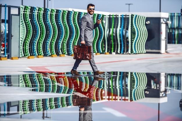 Volle länge des hübschen kaukasischen bärtigen geschäftsmannes im anzug und mit der sonnenbrille, die aktentasche und smartphone hält, während die pfütze überquert.