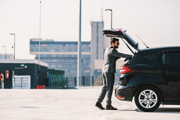 Volle länge des hübschen kaukasischen bärtigen reichen geschäftsmannes im anzug, der kofferraum auf seinem auto öffnet und seine aktentasche hinein legt.
