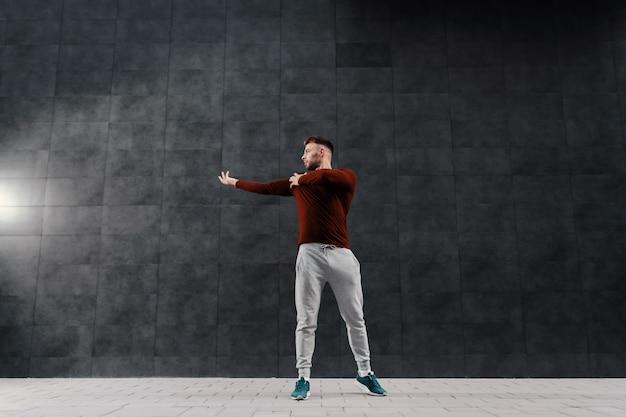 Volle länge des hübschen kaukasischen bärtigen sportlers im trainingsanzug, der aufwärmübungen für arme vor dem laufen macht.