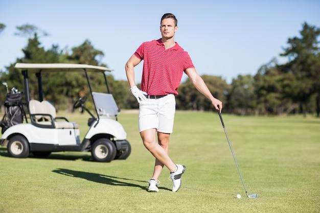 Volle länge des jungen golfers mit der hand auf der hüfte