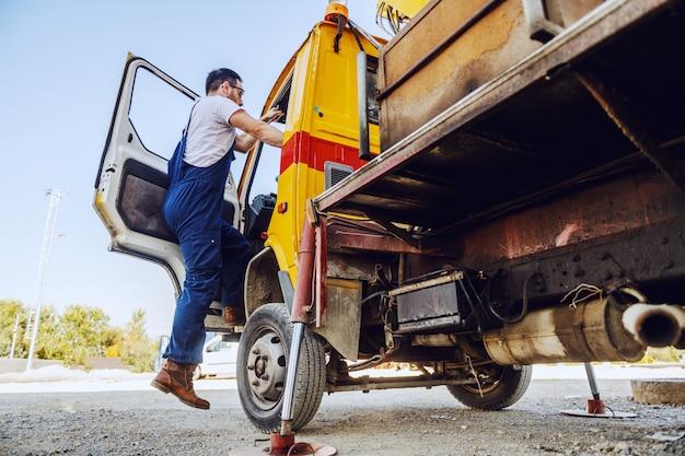 Volle länge des kaukasischen arbeiters in overalls, die bagger betreten. raffinerie außen.