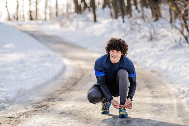 Volle länge des kaukasischen sportlichen mannes, der draußen in sportbekleidung hockt und schnürsenkel bindet. winter fitness konzept.